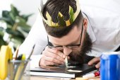 Fotografie businessman with paper crown on head taking drugs at workplace in office