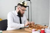 businessman in paper crown sitting at workplace with pizza