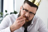 portrait of sad bearded businessman with paper crown on head eating pizza