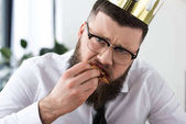 Fotografie portrait of sad bearded businessman with paper crown on head eating pizza