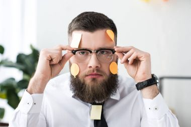 portrait of businessman in eyeglasses with sticky notes on face in office