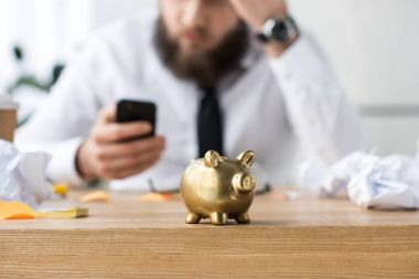 selective focus of piggy bank and businessman with smartphone