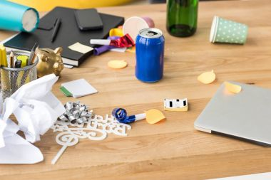close up view of soda drink, party decorations and laptop on tabletop in office