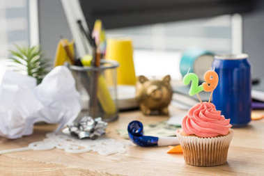 selective focus of birthday cupcake and party decorations at workplace
