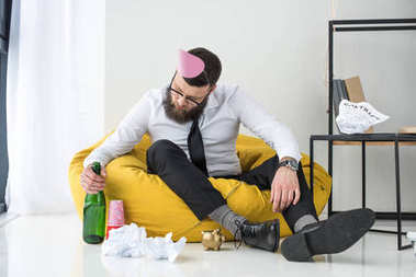 drunk businessman in formal wear with paper cone on head sitting on bag chair