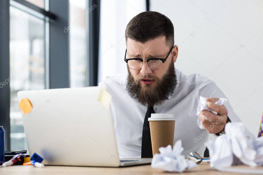 portrait of  overworked businessman at workplace with laptop and coffee to go in office