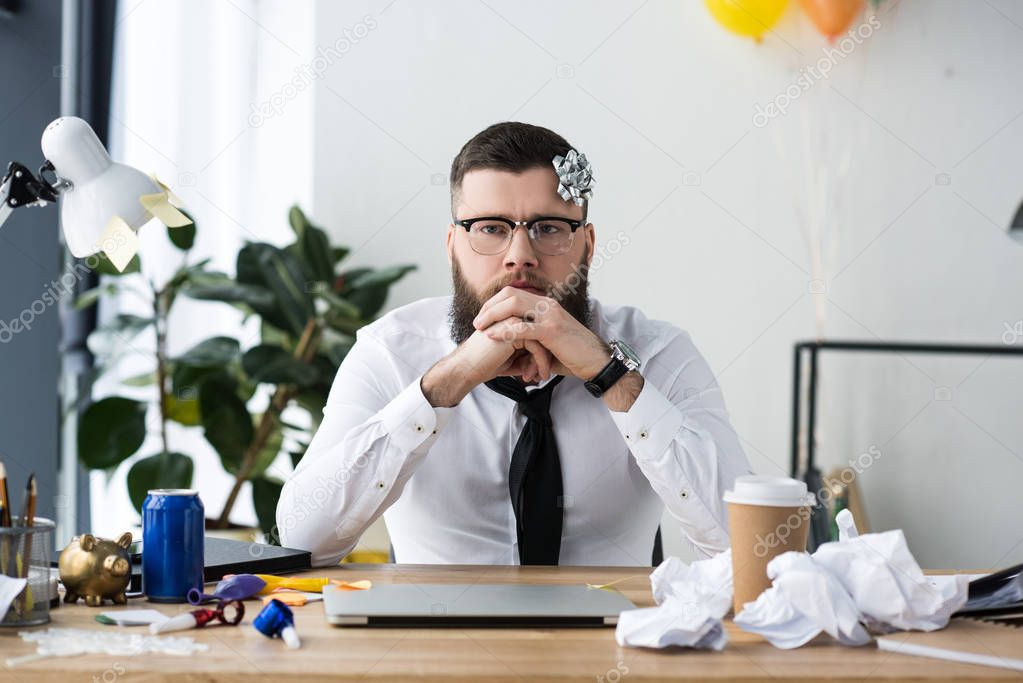 portrait of pensive businessman with bow on head at workplace with laptop