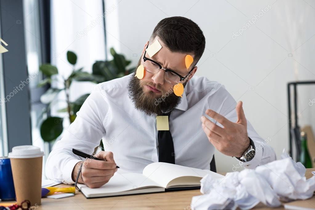 portrait of businessman with sticky notes on face making notes in notebook at workplace