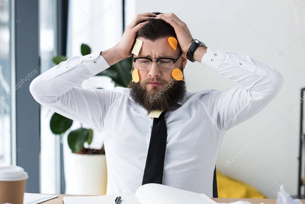 portrait of tired businessman in formal wear with sticky notes on face at workplace in office