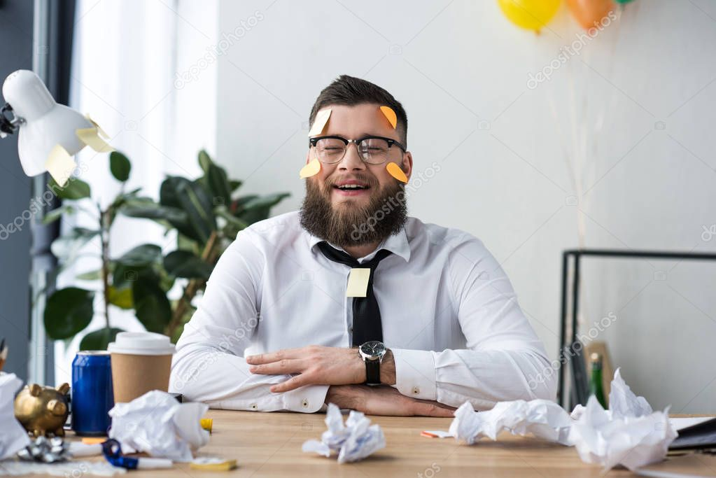 portrait of cheerful businessman in formal wear with sticky notes on face at workplace in office