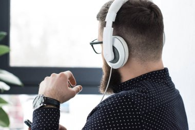partial view of man with smartphone listening music in headphones