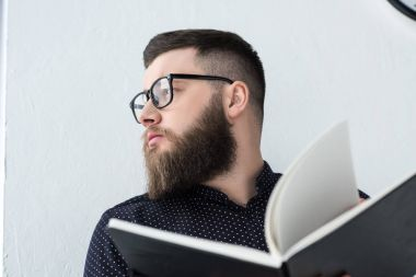 portrait of stylish businessman with notebook looking away
