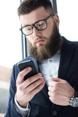 portrait of focused bearded businessman in eyeglasses using smartphone