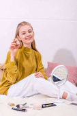 Photo young woman with jar of nail polish sitting in bed at home