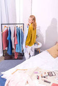 Fotografie high angle view of smiling young woman choosing clothes to wear in bedroom