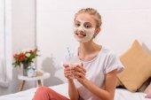 lächelnde junge Frau mit weißer Tonerde Gesichtsmaske mit Milchshake im Einmachglas zu Hause
