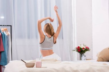 Back view of young woman stretching after wake up with breakfast standing on bed on foreground stock vector