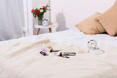close-up shot of makeup supplies lying on bed