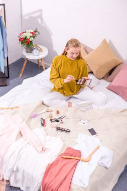 high angle view of young woman opening eye shadows box while sitting on bed