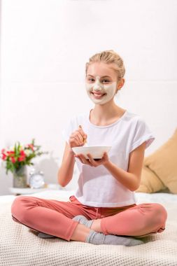happy young woman applying white clay mask on face while sitting on bed