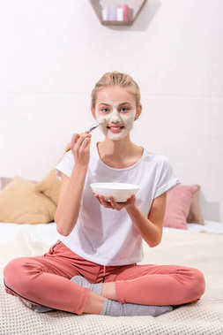 happy young woman applying clay mask on face at home and looking at camera