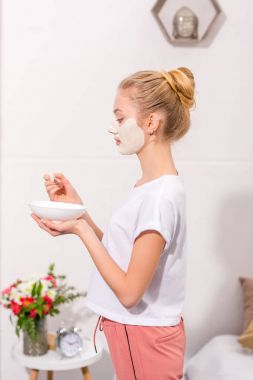 side view of young woman applying clay mask on face at home