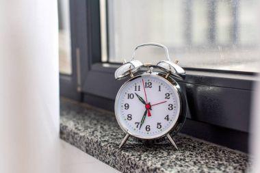 close-up shot of vintage alarm clock on windowsill