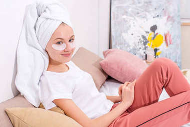 young woman with cosmetic facial patches relaxing in bed at home