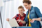 Fotografia bella madre e figlio che fanno e-shopping con computer portatile e carta di credito