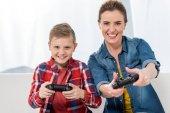 matka a syn hrát videohry s gamepady spolu