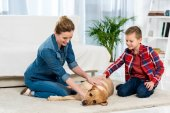 Fotografie mother and son petting their dog while he lying on floor of living room