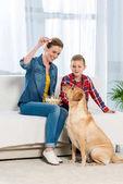Fotografie glückliche Mutter und Sohn füttern ihren Hund mit popcorn