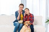 Fotografie Mutter und Sohn Film mit Popcorn, während ihr Hund am Boden