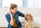 Fotografie woman petting her labrador dog at home