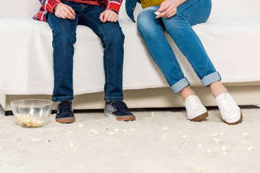 cropped shot of mother and kid sitting on couch with messy spilled popcorn on floor