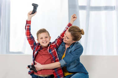 mother embracing her celebrating son while playing video games together