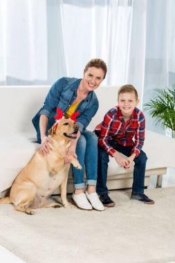 mother and son petting their dog at home