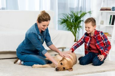 mother and son petting their dog while he lying on floor of living room