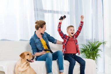 expressive mother and son playing video games while their dog sitting on floor