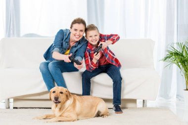 excited mother and son playing video games while their dog sitting on floor and watching