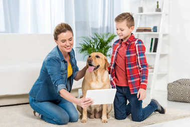 mother and son playing console games while their dog sitting on floor