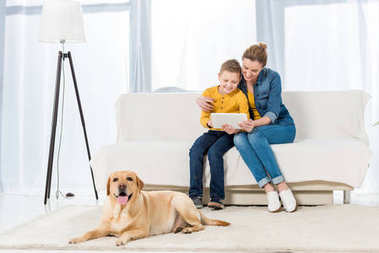 mother and son using tablet together with adorable dog lying on floor on foreground