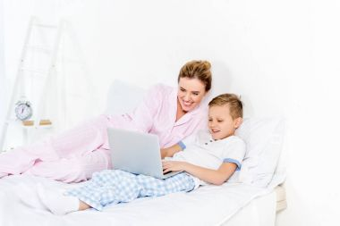 mother and son using laptop together in bed