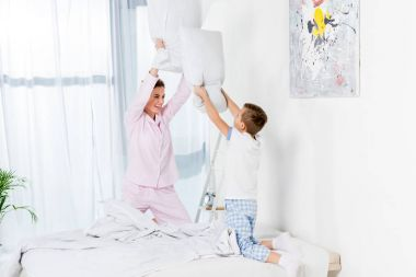 mother and son fighting with pillows in bed on weekend morning