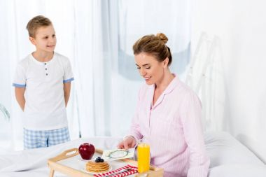 happy little son giving breakfast in bed for mother on mothers day