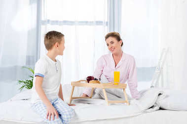little son giving breakfast in bed for mother