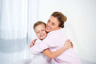 mother and son in pajamas embracing in morning