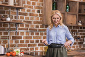 Fotografie attractive woman standing with frying pan and wooden spatula in kitchen