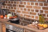 Fotografie pánev a dřevěné špachtle na sporáku v kuchyni