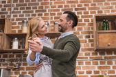 Fotografie lächelnde Frau und Mann in der Küche tanzen